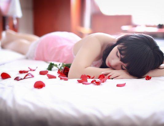 chica en la cama con pétalos de rosa