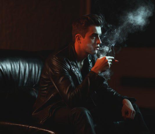 Chico fumando en un sofá