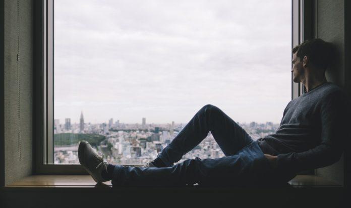 Hombre mirando a la calle desde su ventana