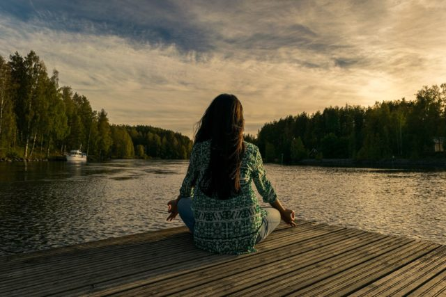 En la imagen se puede observar a una mujer de espaldas practicando un ejercicio de meditación en el borde de un lago, una herramienta ideal para gestionar nuestra ira.