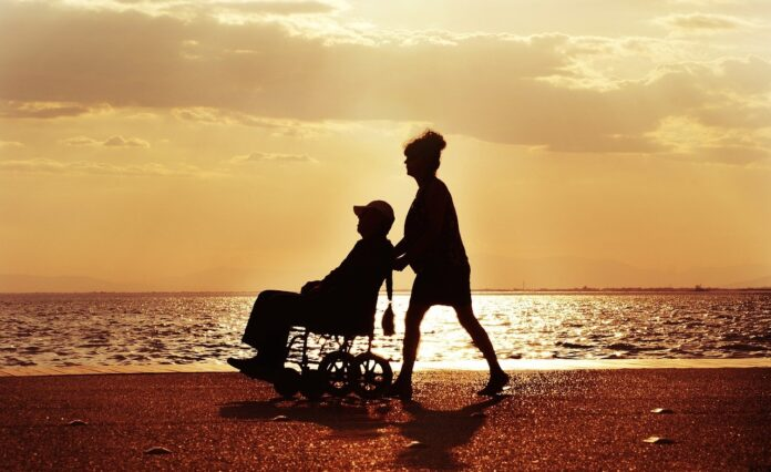 Mujer paseando a un hombre (paciente) en silla de ruedas